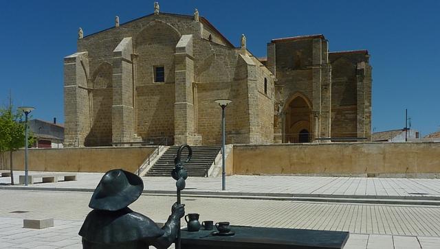 Estatua del mesonero Pablo Payo con la iglesia de Santa María la Blanca al fondo en Villalcázar de Sirga