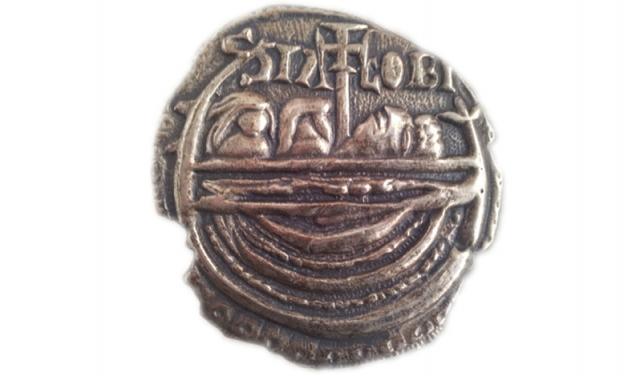 La moneda de Adro Vello mide 13 milímetros de diámetro y está hecha de una aleación de plata y cobre. Data del reinado de Fernando II (1157-1188), impulsor de la construcción de la catedral de Santiago