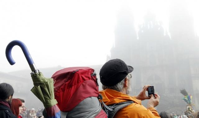 Un peregrino fotografía la catedral de Santiago oculta tras la niebla / Fotografía de Sandra Alonso